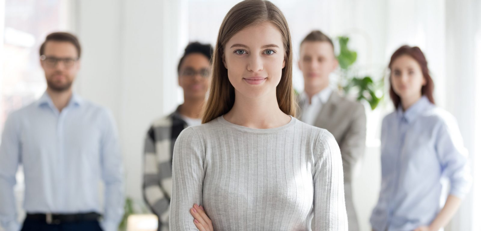 Confident young female leader, office worker, intern or company employee smiling looking at camera with team at background, happy successful businesswoman professional manager business coach portrait